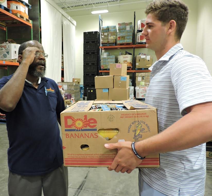 Volunteer Sam Koby of Bayside Academy, right, gets instructions from Ron Henderson, the reclamation coordinator for Feeding the Gulf Coast, on unloading an incoming box of groceries that will be distributed to the needy in Mobile, Alabama . (AHSAA photo)
